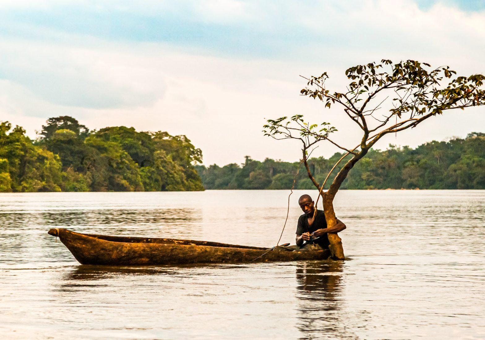 Fisherman in canoe on Moa River, Sierra Leone