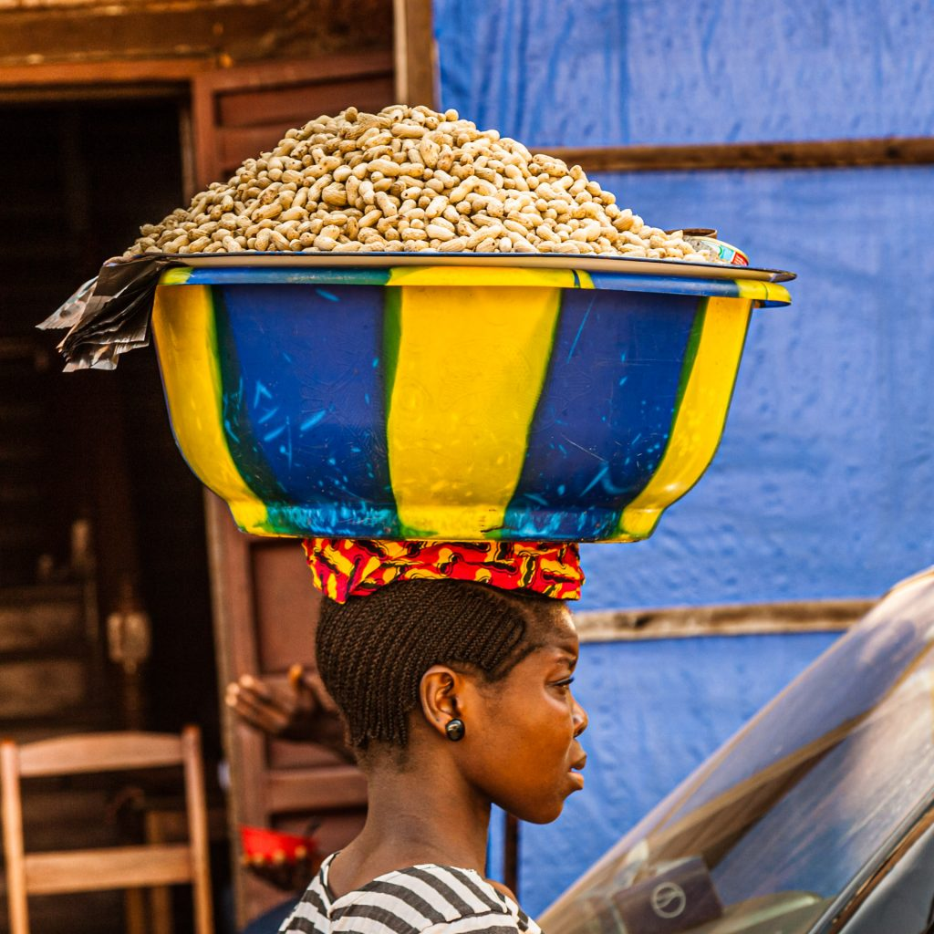 African saleswoman carries a bowl of peanuts on her head