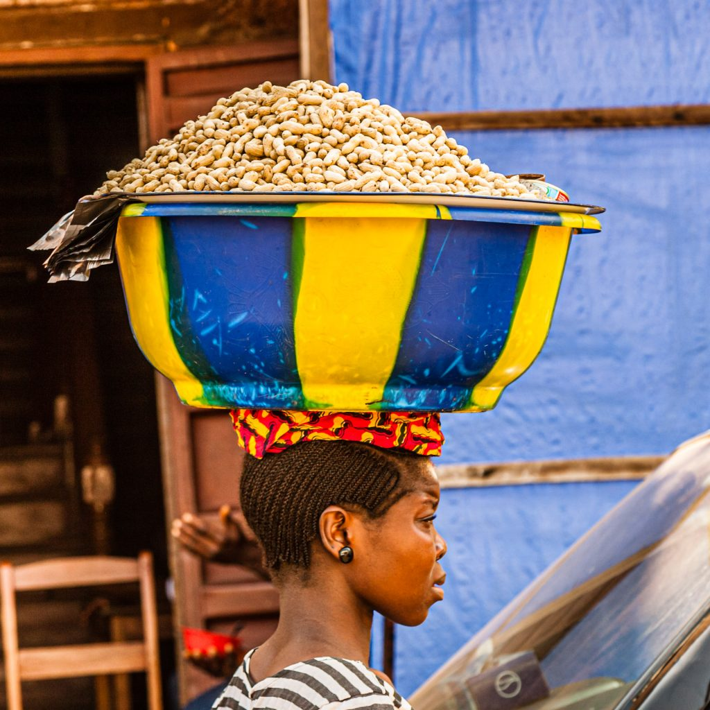 African woman carries bowl of peanuts on her head