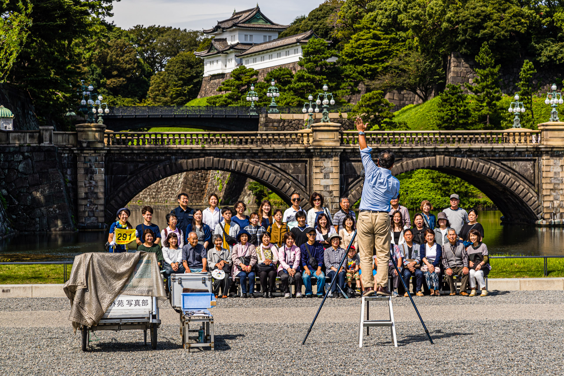 Group photographer demands attention in front of the Japanese Imperial Palace. Photoshooting in front of the Tenno Palace in Chiyoda (Tokyo), Japan